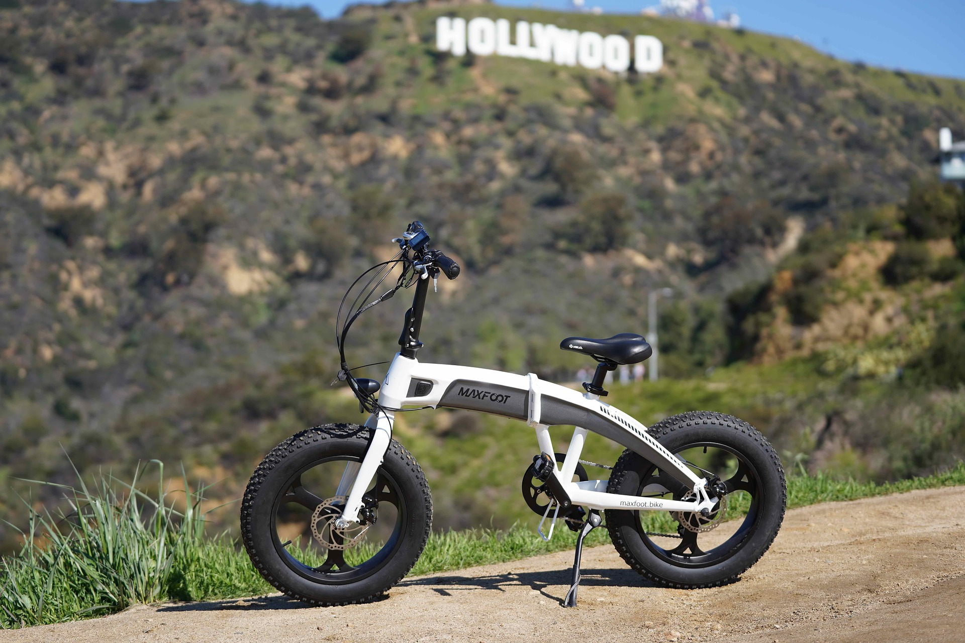 White folding E-bike standing with a Hollywood sign in the background